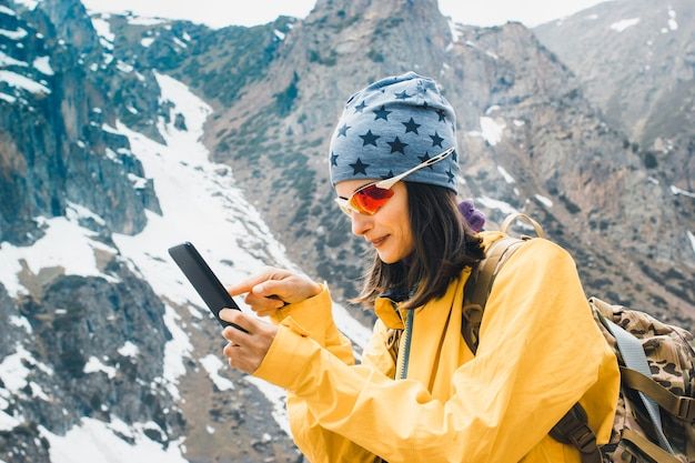 Jeune femme voyageant en tapant un message sur un smartphone dans les montagnes enneigées rocheuses