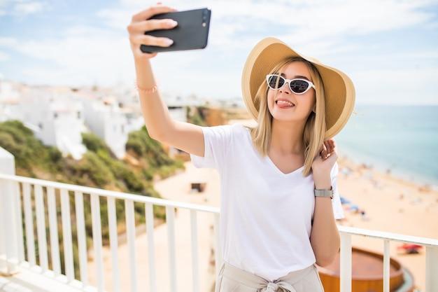 Jeune femme voyageant tenant un téléphone faisant selfie contre mer