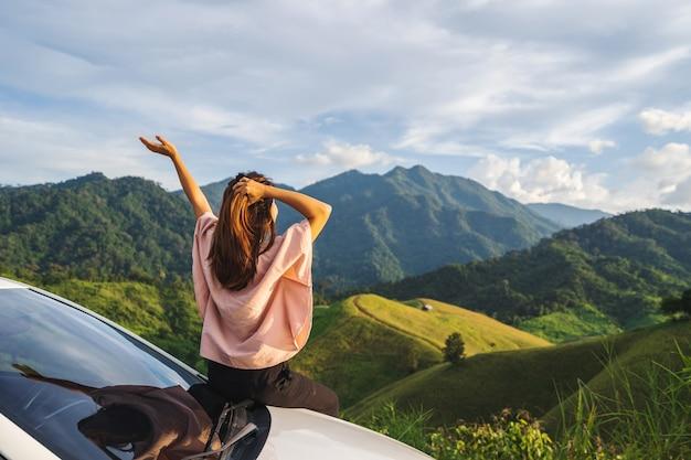 Jeune femme voyageur assis dans une voiture en regardant une belle vue sur la montagne pendant le voyage au volant d'un voyage sur la route en vacances