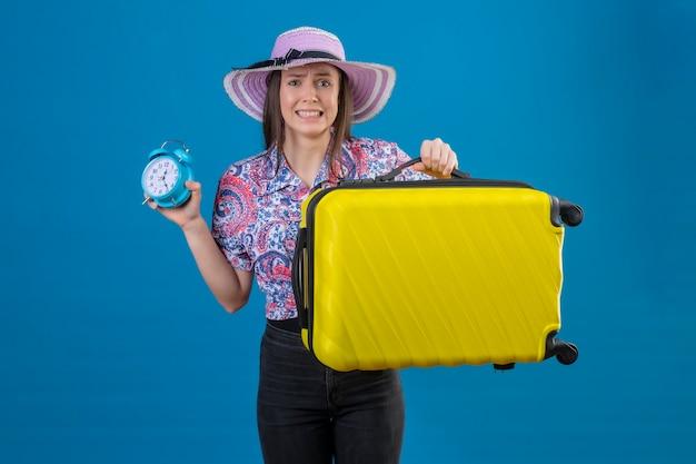 Jeune femme voyageur en chapeau d'été debout avec valise jaune tenant un réveil stressé et nerveux sur fond bleu
