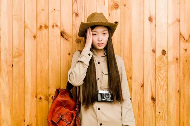 Jeune femme voyageur chinoise fatiguée et très endormie en gardant la main sur la tête.