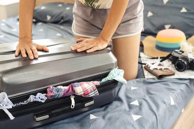 Jeune femme voyageur emballant ses vêtements et des trucs dans la valise, concept de voyage et de vacances