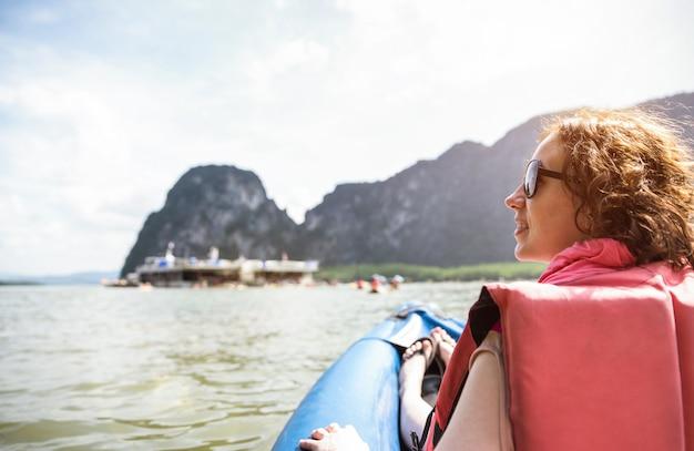 Jeune femme voyageur avec gilet de sauvetage au coucher du soleil monter sur une île de kayak en sautillant