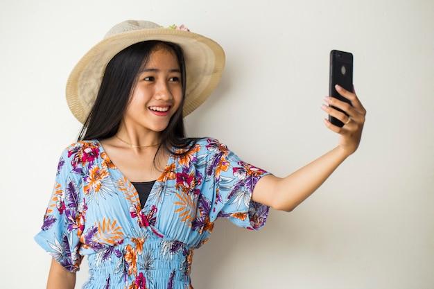 Jeune femme voyageur heureux sourire prendre selfie. sur fond blanc