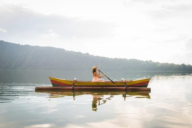 Jeune femme voyageur pagayant sur un bateau en bois à pura ulun danu bratan