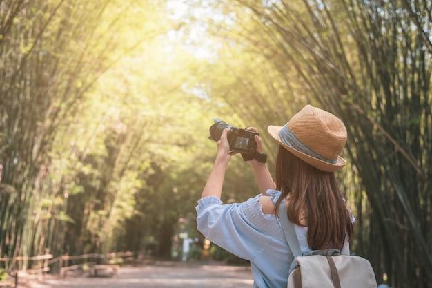 Jeune femme voyageur prenant une photo dans une belle forêt de bambous