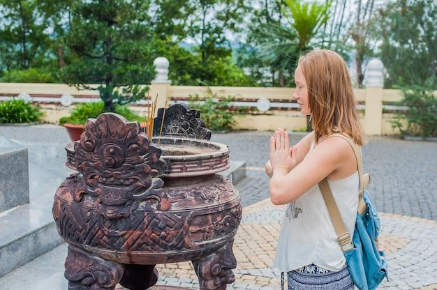 Jeune femme voyageur priant dans une action polie avec des bâtons d'encens au temple du bouddhisme au vietnam