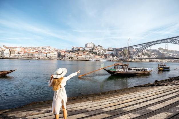 Jeune femme voyageur profitant d'une belle vue sur la ville sur le fleuve douro et les bateaux traditionnels portugais pendant la lumière du matin à porto, portugal