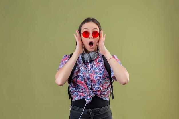 Jeune femme voyageur avec sac à dos et casque portant des lunettes de soleil rouges choqué debout avec la bouche grande ouverte touchant le visage avec les mains sur le mur vert
