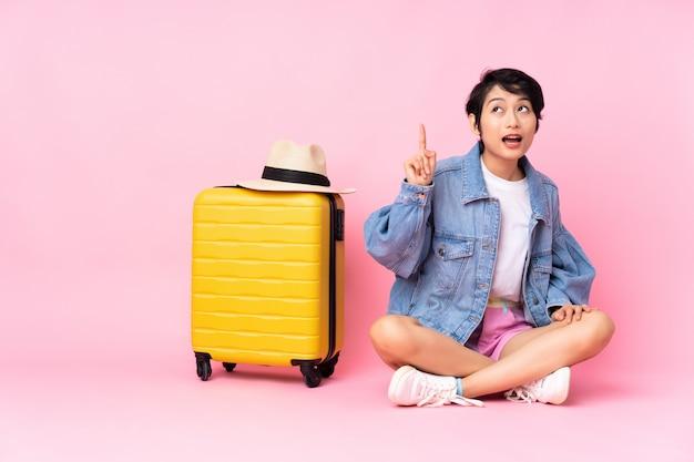 Jeune femme voyageur avec valise assis sur le sol sur rose isolé dans l'intention de réaliser la solution tout en levant un doigt
