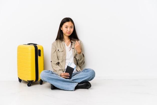 Jeune femme voyageuse chinoise assise tenant une carte d'embarquement pointant avec le doigt vers vous comme si elle vous invitait à se rapprocher.