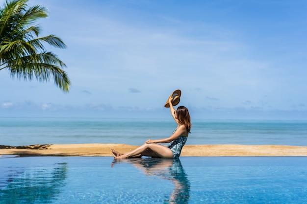 Jeune femme voyageuse se relaxant et profitant d'une piscine tropicale lors d'un voyage pour les vacances d'été, concept de voyage