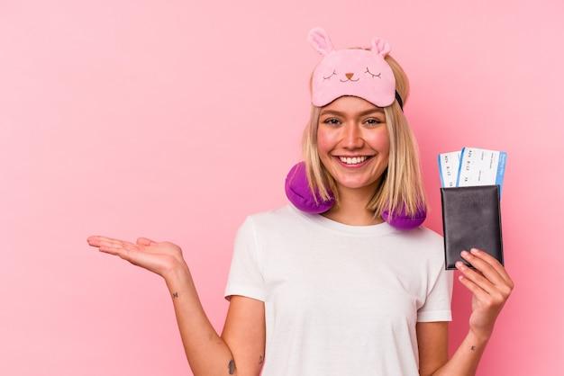 Jeune femme voyageuse vénézuélienne tenant un passeport isolé sur fond rose montrant un espace de copie sur une paume et tenant une autre main sur la taille.