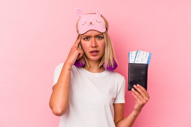 Jeune femme voyageuse vénézuélienne tenant un passeport isolé sur fond rose montrant un geste de déception avec l'index.