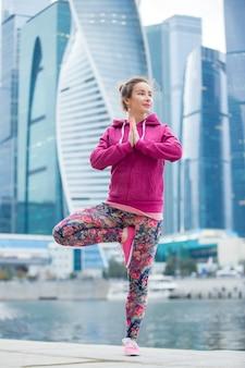 Une jeune femme à vrksasana pose contre les gratte-ciel