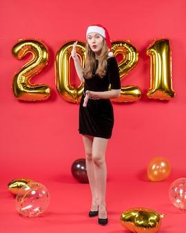 Jeune femme vue de face avec des ballons de bonnet de noel sur rouge