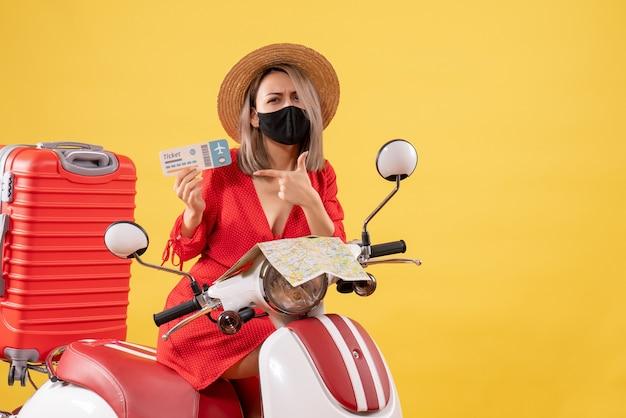 Jeune femme vue de face sur un cyclomoteur avec une grosse valise tenant un billet