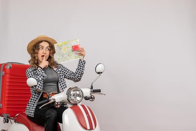 Jeune femme vue de face sur un cyclomoteur tenant une carte et une carte