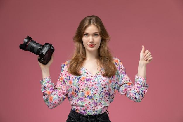 La jeune femme vue de face montre que tout va bien à propos de la photocaméra