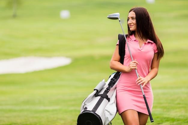Jeune femme vue de face sur le parcours de golf