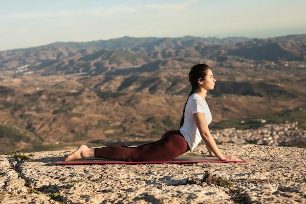 Jeune femme vue de face sur tapis pratiquant le yoga