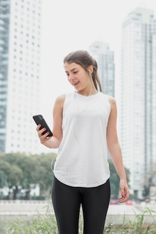 Jeune femme vue de face vérifiant son téléphone