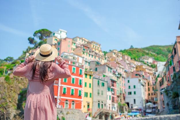 Jeune femme avec une vue magnifique sur le vieux village de riomaggiore, cinque terre, ligurie