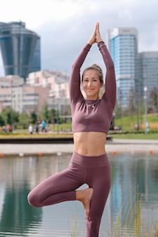 Jeune femme en yoga arbre pose et souriant avec la ville.