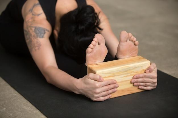 Jeune femme yogi en paschimottanasana pose avec bloc, close up