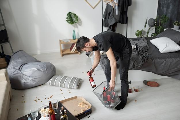 Jeune fêtard jetant des bouteilles d'alcool vides dans la poubelle tout en nettoyant la salle après la fête