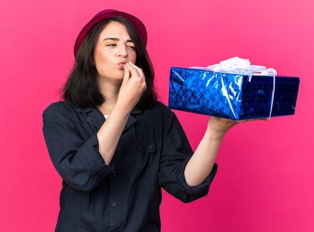 Jeune fêtarde caucasienne portant un chapeau de fête tenant et regardant un paquet cadeau faisant le geste de baiser du chef isolé sur un mur rose