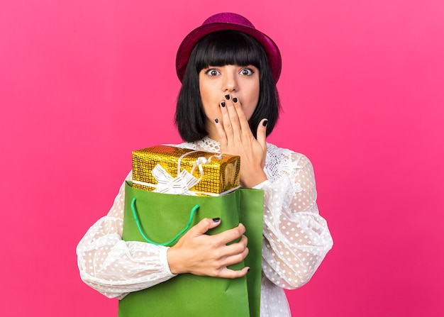 Jeune fêtarde concernée portant un chapeau de fête tenant un paquet cadeau dans un sac en papier gardant la main sur la bouche isolée sur un mur rose avec espace de copie