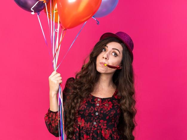 Jeune fêtarde impressionnée portant un chapeau de fête tenant des ballons soufflant une corne de fête en regardant le côté isolé sur un mur rose avec un espace de copie