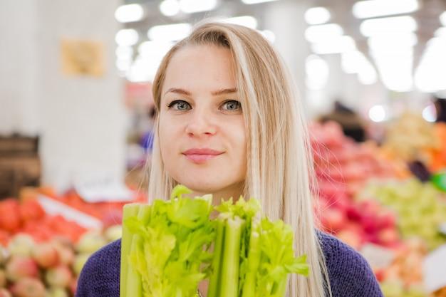 Jeune fille achète des légumes au marché