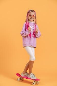 Jeune fille active en chemise rose et short blanc debout sur une planche à roulettes