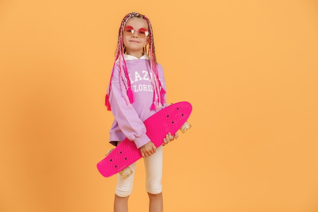Jeune fille active en chemise rose et short blanc tenant une planche à roulettes sur fond jaune