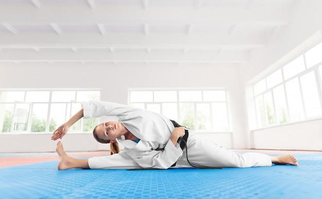 Jeune fille active, faire de l'exercice sur la flexibilité dans la salle de sport légère.