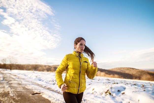 Jeune fille active sportive motivée et concentrée avec une queue de cheval moelleuse dans des vêtements de sport d'hiver courir dans la nature enneigée sur la route.