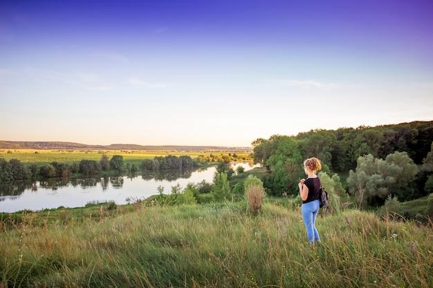 La jeune fille admire la beauté de la nature. paysage d'été avec rivière et forêt