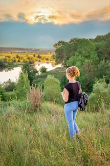 Une jeune fille admire la nature au coucher du soleil. mode de vie sain, rester dans la nature