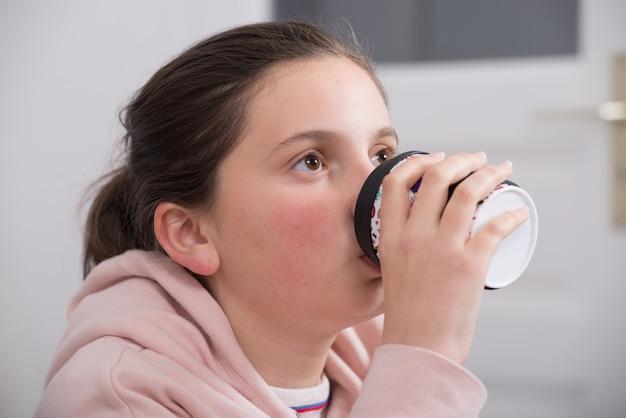 Jeune fille adolescente belle avec une tasse de café en papier