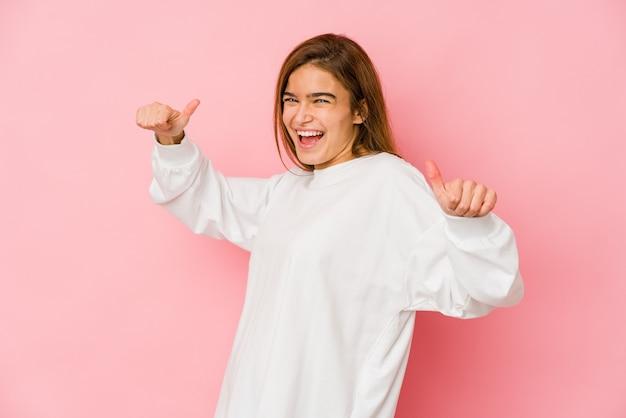 Jeune fille adolescente caucasienne maigre levant les deux pouces vers le haut, souriante et confiante.