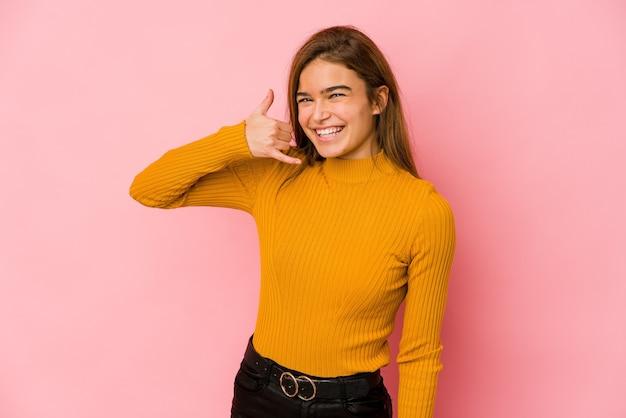 Jeune fille adolescente caucasienne maigre montrant un geste d'appel de téléphone mobile avec les doigts.