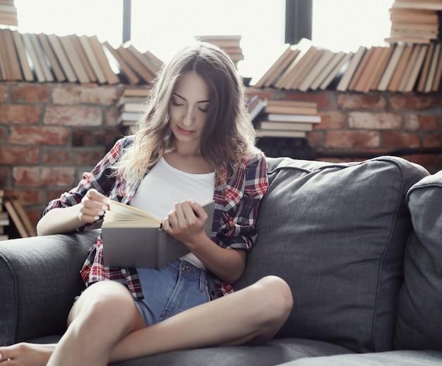 Jeune fille adolescente lisant un livre à la maison