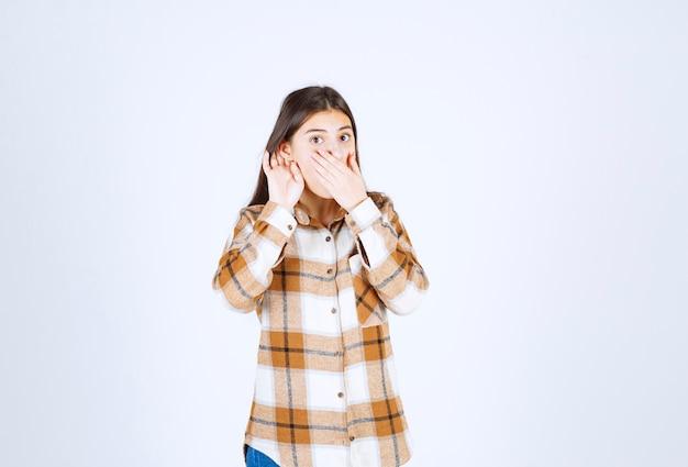 Jeune fille adorable dans des vêtements décontractés écoutant quelque chose sur un mur blanc.