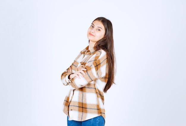 Jeune fille adorable dans des vêtements décontractés posant sur un mur blanc.