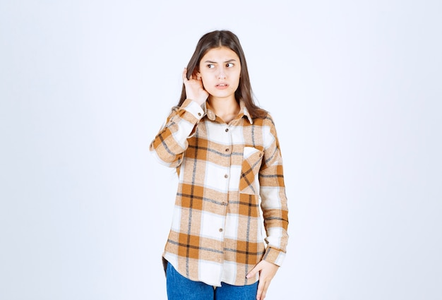 Jeune fille adorable dans des vêtements décontractés se présentant à la caméra sur un mur blanc.