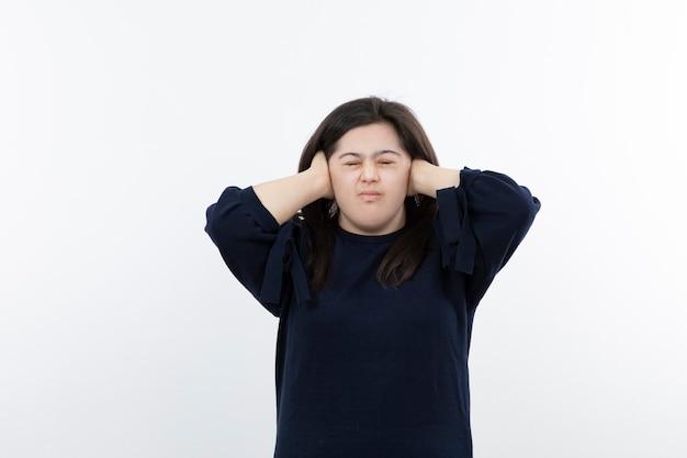 Jeune fille adorable avec le syndrome de down couvrant ses oreilles.