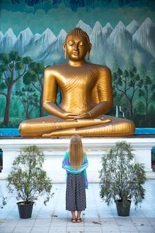 La jeune fille adore le bouddha