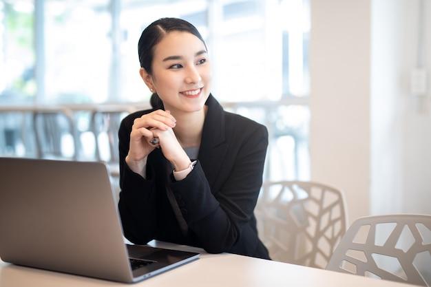 Jeune fille d'affaires asiatique travaillant avec un ordinateur portable dans un café-restaurant, souriant regarder ailleurs.